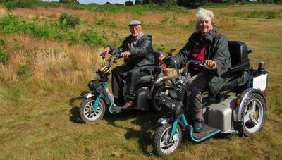 Man and woman on mobility scooters admiring the country view