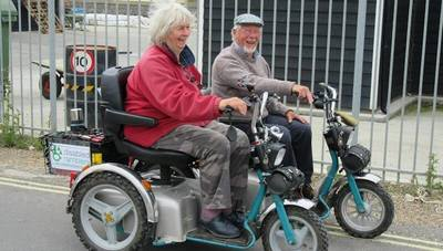 Man and woman on mobility scooters