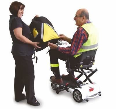 Woman hands man on mobility scooter a TGA reflective Safety Bag