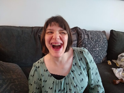 Photo of Tricia wearing a green top and sitting on a couch laughing