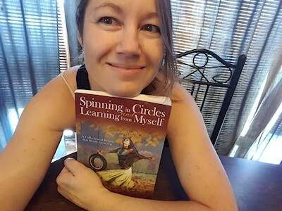 Author Tsara Shelton holding a copy of her book Spinning in Circles and Learning From Myself