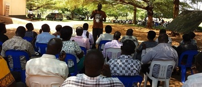A man who is standing outdoors teaches a group of seated people in Uganda.