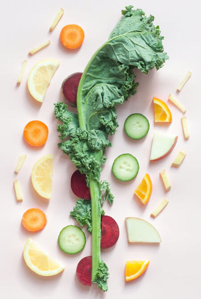 Slices of fruit and a stalk of kale on a pinkish white colored background - Photo by Dose Juice on Unsplash.
