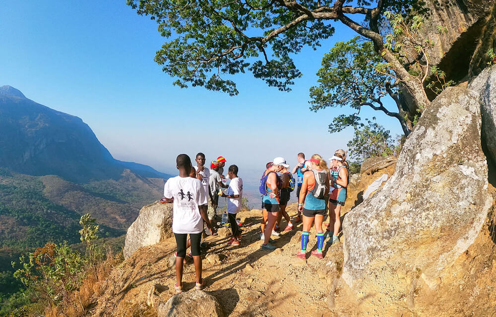 Water Stop Point on Trail Run in Southern Malawi - A group of people take a break on a mountain trail overlooking a valley.