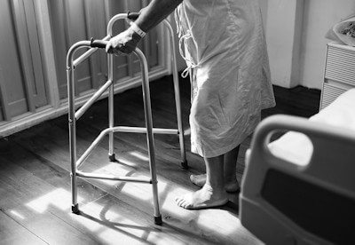 Black and white photo of a person using a walking aid.