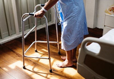 Man standing using adult walker frame inside room - Photo by rawpixel on Unsplash.