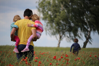 A man in a yellow T-shirt carrying two small girls walking in a field of red petaled flowers, a small boy runs ahead of them towards two trees - Photo by Juliane Liebermann on Unsplash.