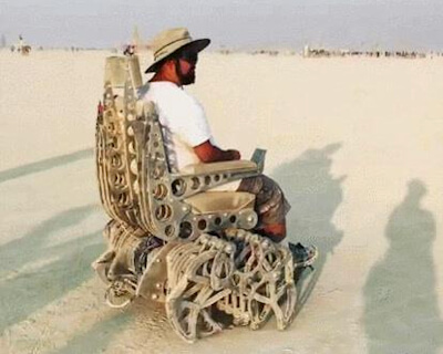 Man seated in a walking wheelchair as seen at Burning Man.