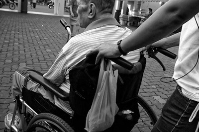 Black and white photo of a man in a wheelchair being pushed by his carer.