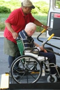 Assisting man in wheelchair into a van