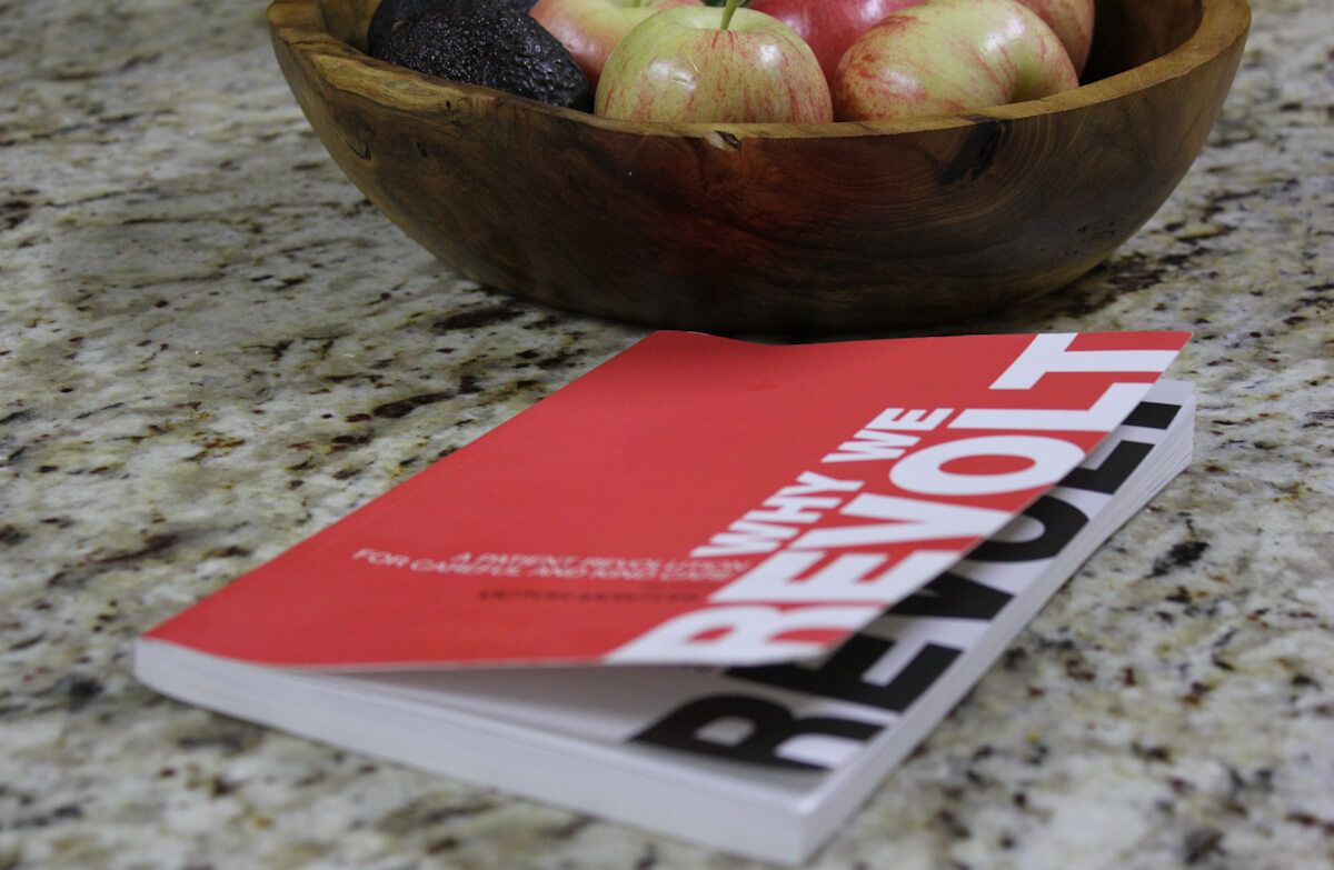 Image shows the book cover of Why We Revolt: A Patient Revolution for Careful and Kind Care. A wooden bowl containing fruit is also pictured on the counter top in the background.