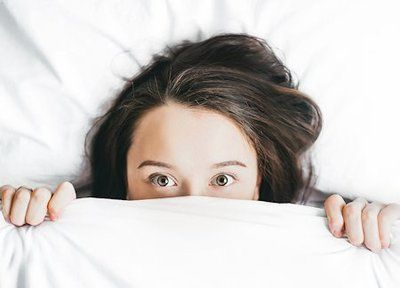 Young woman in bed, unable to sleep, with covers pulled up to her nose and eyes wide open.