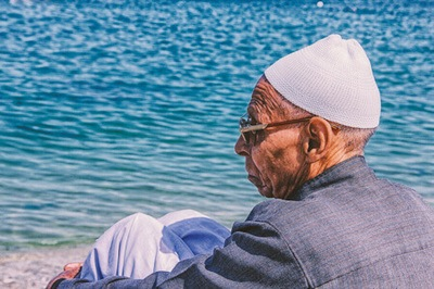 Wrinkled elderly man wearing a hat sitting on a sunny beach.