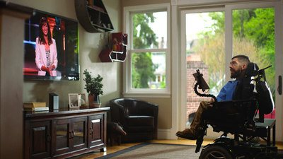 Man in a wheelchair navigates the channels on a large screen TV in his lounge room by using Comcast X1 eye control.