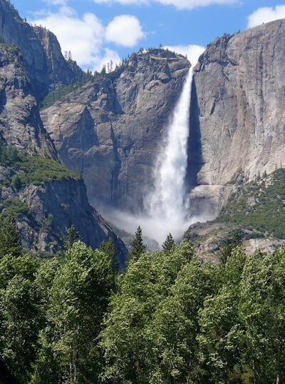 An impressive waterfall tumbling down from a vertical rock face in Yosemite National Park America.